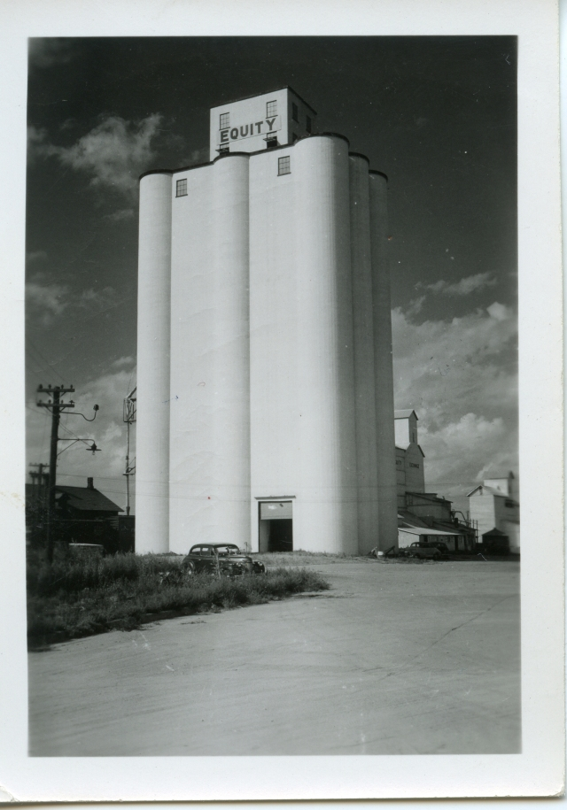 In this photo dated 1951, an old wooden elevator stands immediately behind the concrete house. It was demolished to make room for the second bank of concrete bins, built in 2000.