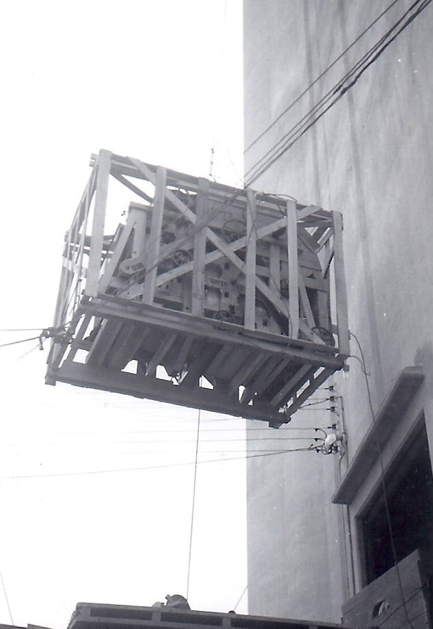 "In this 1950 photo from Neil Lieb's archive, he explains what we see inside a crate that's being hoisted to the top of the Alta, Iowa, grain elevator. ""That's the motor for the belt and probably the gearbox,"" he says. ""We didn't take it out of the crate till we got it on top because the crate was designed so we could lift it. That little crane could hold a lot of weight."