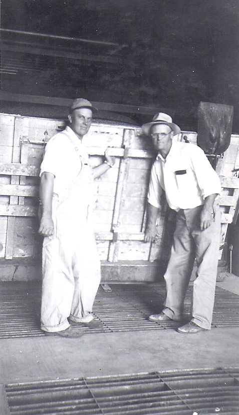 First load of grain being dumped in the elevator. Man on left is probably an elevator employee, Bill Russell, right.